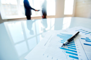 Business documents with charts on the table with business people in the background